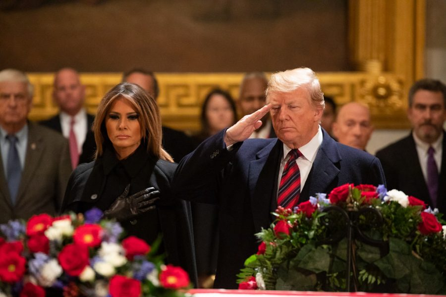 Photo Credit: Photo via Flicker Images under the creative commons license. President Donald J. Trump, joined by First Lady Melania Trump, salutes at the casket of former President George H. W. Bush.
