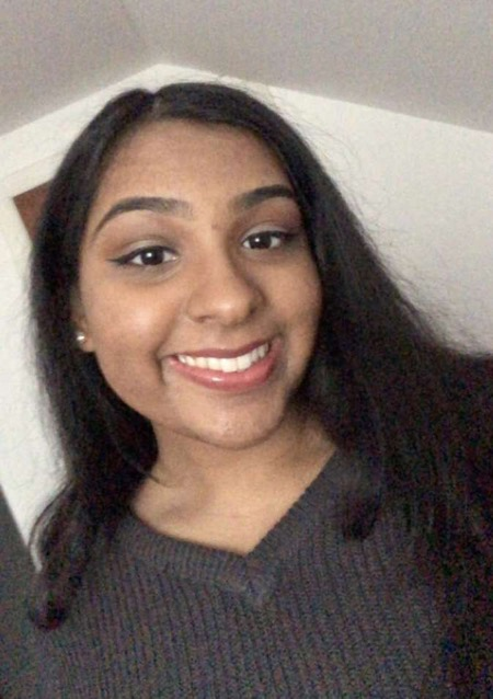 Astha Patel smiles for the camera as she takes a selfie.