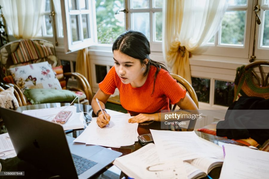 A student works on assignment in her room. All rights reserved under the creative commons license. Getty images.